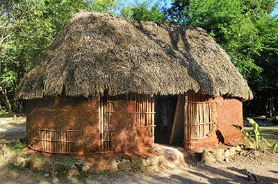 While the wealthy of socially prominent may have had adobe homes, the most common house structure in Central America was that of a thatched-roof hut. Image via Adobe Stock.