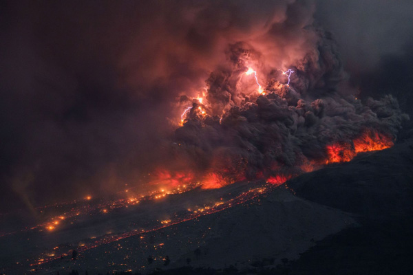 A lightning storm erupts inside the ash cloud of an erupting volcano in Indonesia. Image via mirror.co.uk