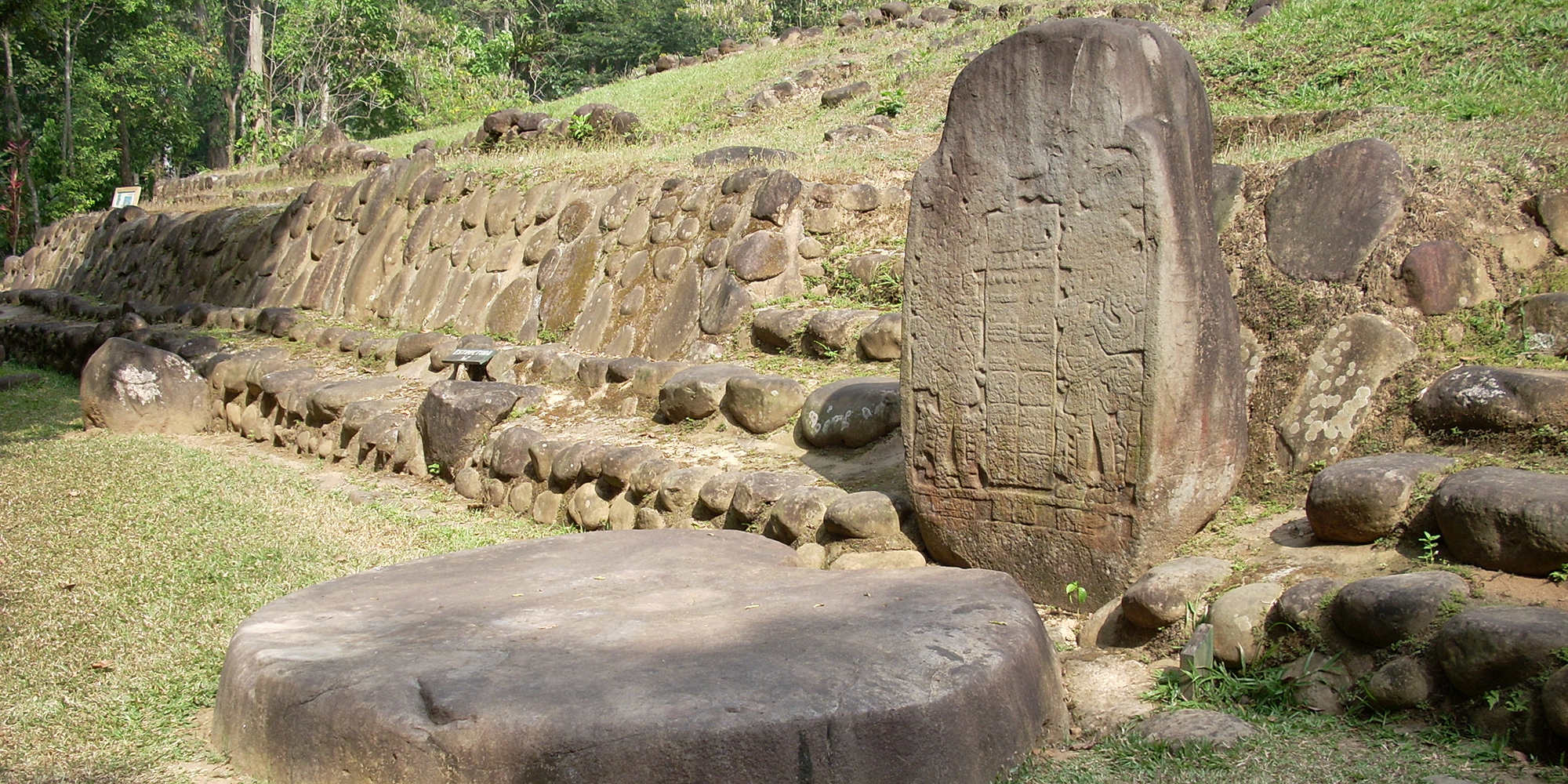 Stela 5 at Takalik Abaj, El Asintal, Retalhuleu, Guatemala, showing an early example of a Long Count date. Altar 8 lies before it. Image via wikimedia Commons