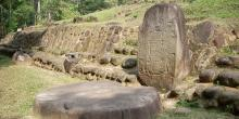 Stela 5 at Takalik Abaj, El Asintal, Retalhuleu, Guatemala, showing an early example of a Long Count date. Altar 8 lies before it. Image via wikimedia Commons